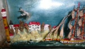 Details of ship in bottle with sailing ship, U-boat, airplane, village all visible
