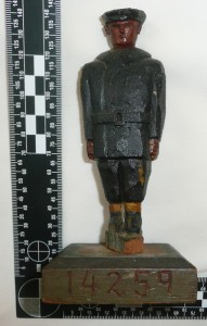 A primitive style wooden carving of a man dressed in navy pea-jacket and cap, mounted on a block of wood, recognizably a piece of folk art with discernible details (cap,boots, trousers, jacket)