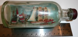 "A sailing ship in a bottle with blue background. Red script with letters missing says ""Shilo, Manitoba"""