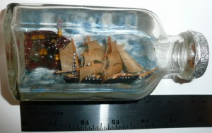 Clear glass bottle lying on its side, mouth to the right. Inside is a sailing ship with 3 masts in full sail, a village behind.